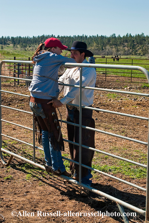 Cowboy Lee Monk and fiance Shelby Field share a moment of affection at branding, eastern Montana, MODEL RELEASED