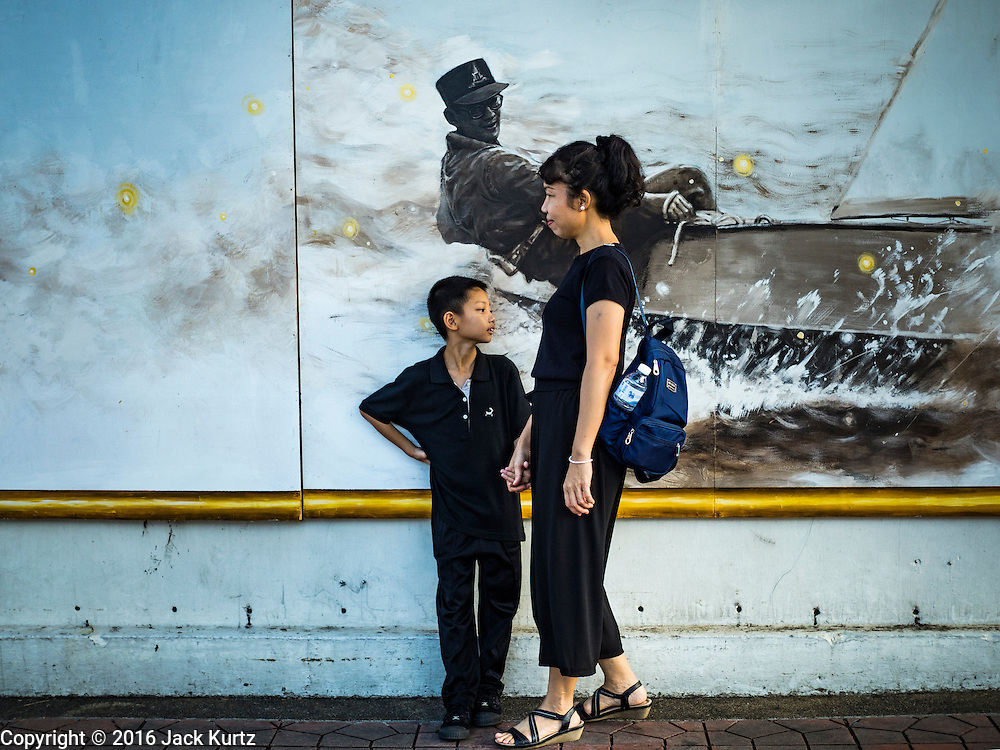 20 OCTOBER 2016 - BANGKOK, THAILAND: A mother and child dressed in mourning clothes fro the late Bhumibol Adulyadej, the King of Thailand, stand in front of picture of the King in a small sailboat. The King died Oct. 13, 2016. He was 88. His death came after a period of failing health. Bhumibol Adulyadej was born in Cambridge, MA, on 5 December 1927. He was the ninth monarch of Thailand from the Chakri Dynasty and is also known as Rama IX. He became King on June 9, 1946 and served as King of Thailand for 70 years, 126 days. He was, at the time of his death, the world's longest-serving head of state and the longest-reigning monarch in Thai history.       PHOTO BY JACK KURTZ
