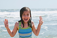 Girl age 6, runs from the cold water.