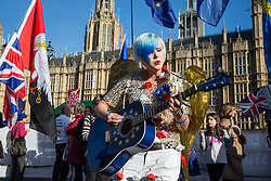 London, UK. 14th February, 2019. Madeleina Kay, also known as EU Super Girl, entertains anti-Brexit activists protesting outside the Houses of Parliament in Westminster.