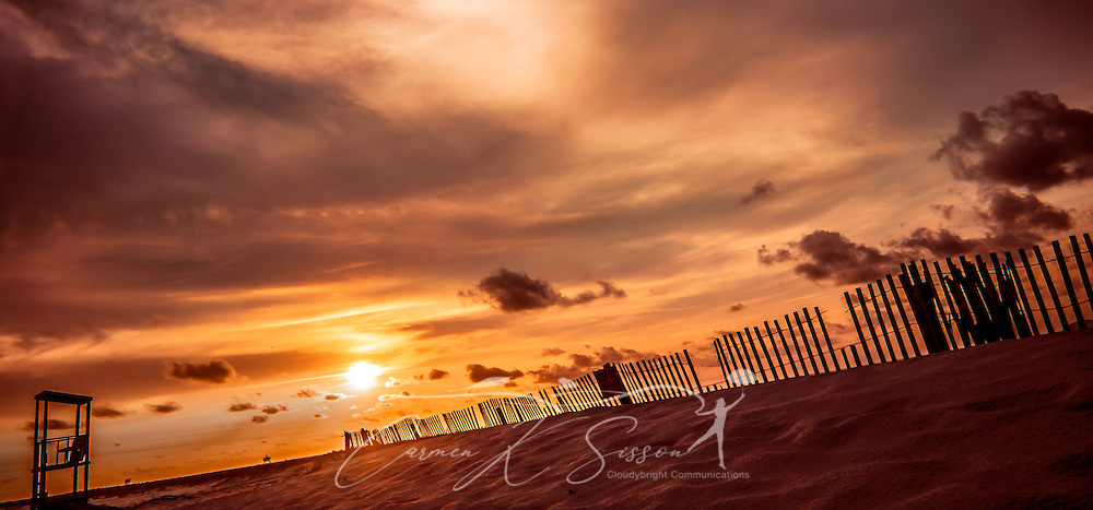 The sun sets behind a wooden-slatted sand fence on the west end of Dauphin Island in Alabama. Sand fences are used for erosion control. (Photo by Carmen K. Sisson/Cloudybright)