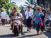 15 JULY 2016 - UBUD, BALI, INDONESIA:       People walk into a prayer ceremony at the community wide mass cremation in Ubud. Local people in Ubud exhumed the remains of family members and burned their remains in a mass cremation ceremony Wednesday. Thursday was spent preparing for Saturday's ceremony that concludes the cremation. Almost 100 people will be cremated and laid to rest in the largest mass cremation in Bali in years this week. Most of the people on Bali are Hindus. Traditional cremations in Bali are very expensive, so communities usually hold one mass cremation approximately every five years. The cremation in Ubud will conclude Saturday, with a large community ceremony.    PHOTO BY JACK KURTZ