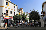 People sitting outdoors tables and chairs of restaurants in old part of city centre, Cordoba, Spain