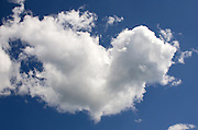 Fluffy white clouds in deep blue sky