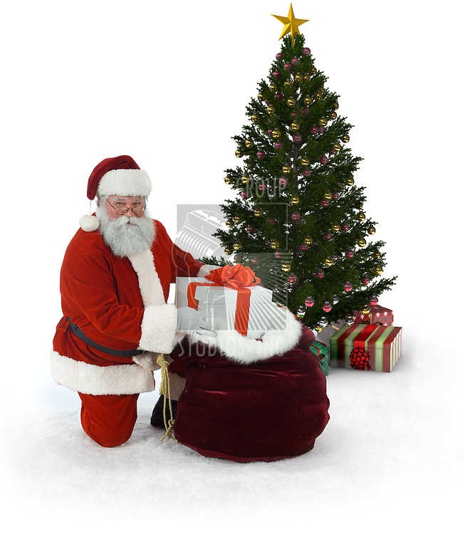 Santa next to a Christmas tree  unloading presentsfrom his sack of gifts on a white background