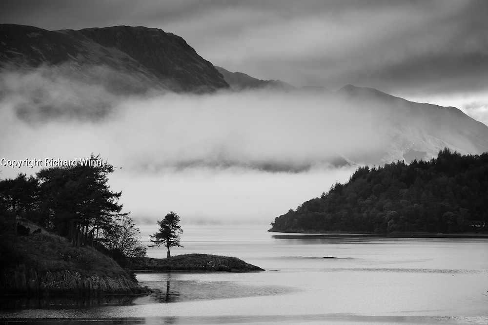 Black and white image of Loch Leven, with Eilean Munde (Isle of the Dead) in the foreground, as mist rolls in from the direction of Kinlochleven.