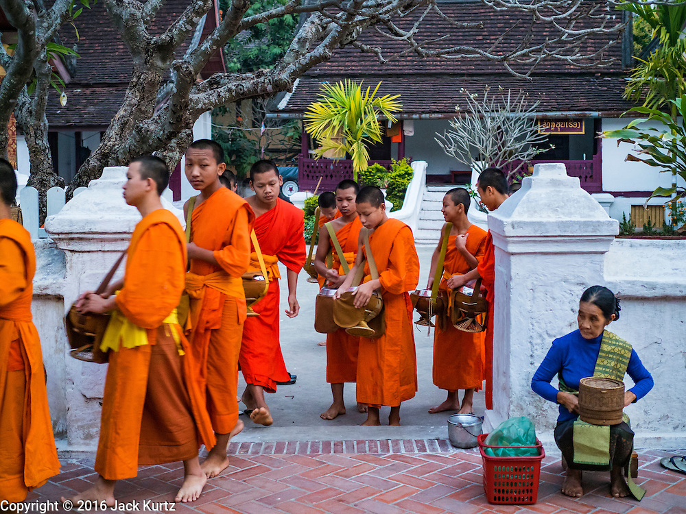 """11 MARCH 2016 - LUANG PRABANG, LAOS: Monks leave their temple in Luang Prabang for the tak bat while a Lao woman waits for monks to pass her. Luang Prabang was named a UNESCO World Heritage Site in 1995. The move saved the city's colonial architecture but the explosion of mass tourism has taken a toll on the city's soul. According to one recent study, a small plot of land that sold for $8,000 three years ago now goes for $120,000. Many longtime residents are selling their homes and moving to small developments around the city. The old homes are then converted to guesthouses, restaurants and spas. The city is famous for the morning """"tak bat,"""" or monks' morning alms rounds. Every morning hundreds of Buddhist monks come out before dawn and walk in a silent procession through the city accepting alms from residents. Now, most of the people presenting alms to the monks are tourists, since so many Lao people have moved outside of the city center. About 50,000 people are thought to live in the Luang Prabang area, the city received more than 530,000 tourists in 2014.       PHOTO BY JACK KURTZ"""