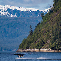 A float plane lands on the water in Punchbowl Cove, Rudyerd Bay, Misty Fjords National Monument,  Southeast Alaska.