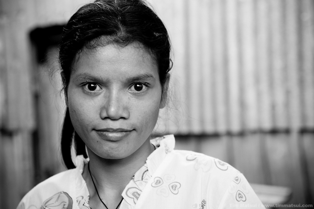 "Srey Bee, a prostitute living in a slum where ""Acting for Women in Distressing Situations"" (AFESIP) conducts outreach and provides services, in Phnom Penh, Cambodia. The slum's permanent structure, a decaying four story building known simply as 'The Building', was built in the 1960's as transitional housing and now hosts a shantytown where many of the city's poor live, including many prostitutes, and is believed to have the highest rate of HIV infection in the city. AFESIP hands out free condoms, instructs prostitutes on HIV prevention, and conducts outreach in case the prostitutes need medical services, choose to leave their profession, or can report on cases of sex trafficking. AFESIP offers housing, education, training, and counseling for women who are victims of sex trafficking, worked as prostitutes, or are escaping domestic violence. Founded by Somaly Mam, who herself was once a prostitute and victim of trafficking and domestic abuse, AFESIP has three facilities in Cambodia and works with other NGO's to provide long term care for the women."