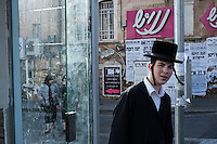 A young Orthodox Jewish man walks along Mea Sharim St in Jerusalem
