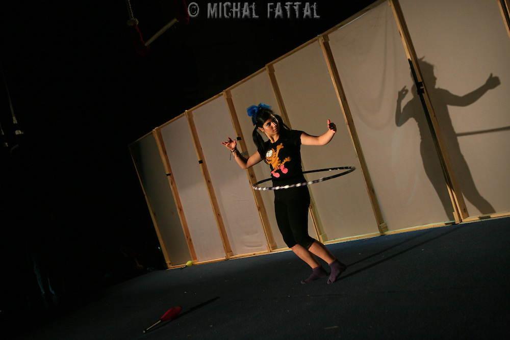 """A Palestinian Circus School member practices next to a set that symbolizes the separation wall, before performing the show """"Circus behind the wall"""" in Ramallah, November 20, 2009. The circus group was established in 2006, in order to give a new way of expression for Palestinians, and a new way to deliver the idea of resistance to the occupation. This performance shows the life of Palestinians behind the separation wall. Photo by Michal Fattal/Backyard"""