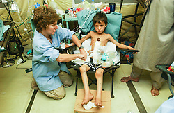 Capt. Libby Dillon from Ripley, W. Va., treats Khan Azam, 5,in an American military hospital at Bagram in Afghanistan  after they were injured from playing with unexploded ordinances  August  9, 2002.    (photo by Ami Vitale)