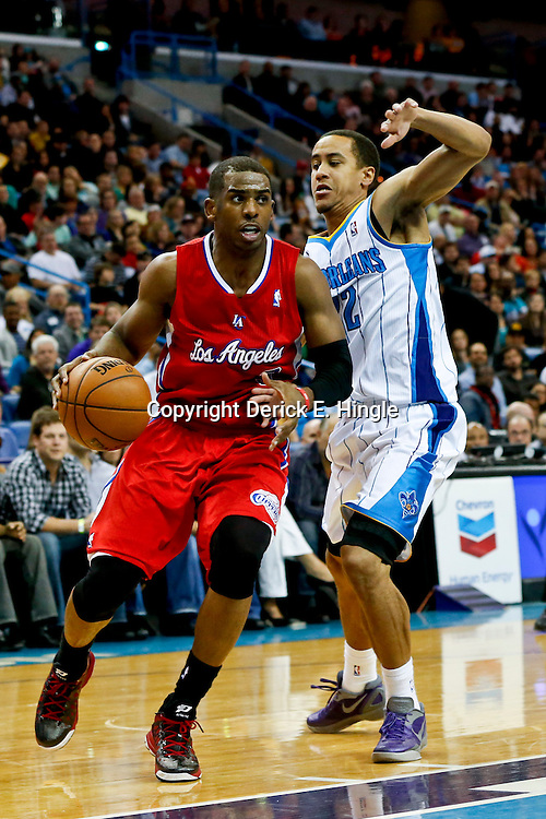 Mar 27, 2013; New Orleans, LA, USA; Los Angeles Clippers point guard Chris Paul (3) drives past New Orleans Hornets point guard Brian Roberts (22) during the second half of a game at the New Orleans Arena. The Clippers defeated the Hornets 105-91. Mandatory Credit: Derick E. Hingle-USA TODAY Sports