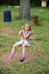Young girl with one shoe on sitting on a rope swing