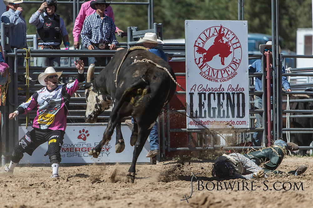 Bull rider Jacob Hanks has a rough ride on Salt River Rodeo's B4 Third Wheel in the first performance of the Elizabeth Stampede on Saturday, June 2, 2018. Bullfighter Nate Jestes steps in to help.