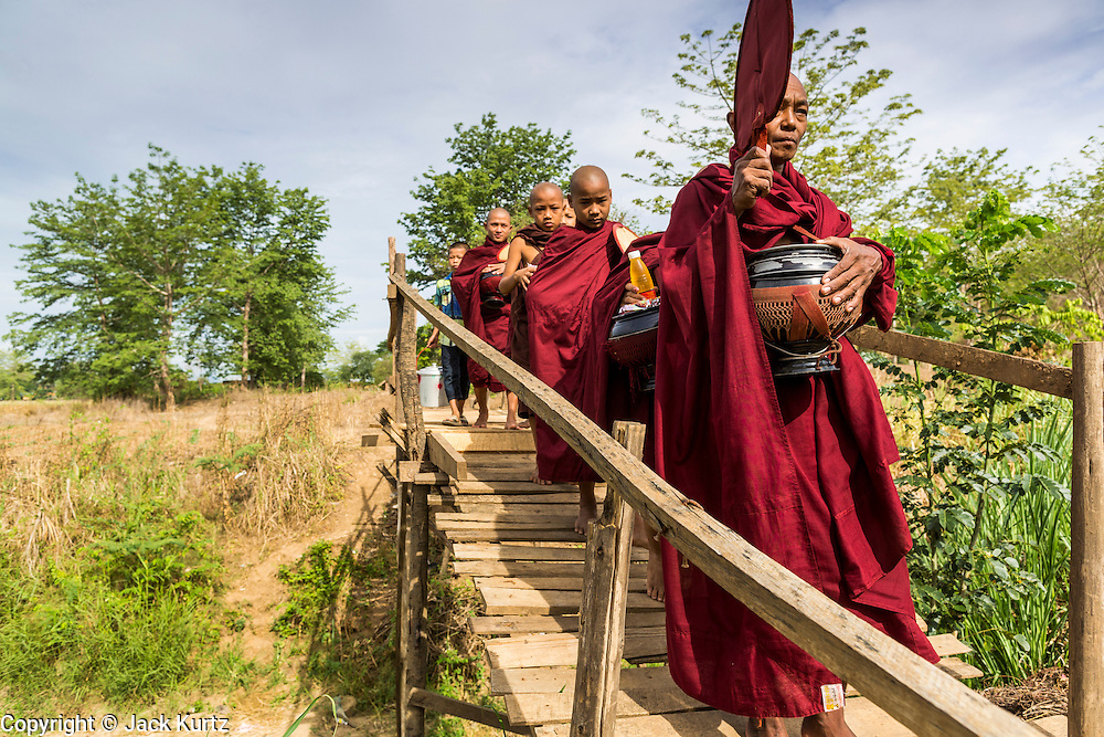 25 MAY 2013 - MAE SOT, TAK, THAILAND:  A Burmese monk leads novices over a wooden bridge during their morning alms rounds through an unofficial village of Burmese refugees north of Mae Sot, Thailand. They live on a narrow strip of land about 200 meters deep and 400 meters long that juts into Thailand. The land is technically Burma but it is on the Thai side of the Moei River, which marks most of the border in this part of Thailand. The refugees, a mix of Buddhists and Christians, settled on the land years ago to avoid strife in Myanmar (Burma). For all practical purposes they live in Thailand. They shop in Thai markets and see their produce to Thai buyers. About 200 people live in thatched huts spread throughout the community. They're close enough to Mae Sot that some can work in town and Burmese merchants from Mae Sot come out to their village to do business with them.   PHOTO BY JACK KURTZ