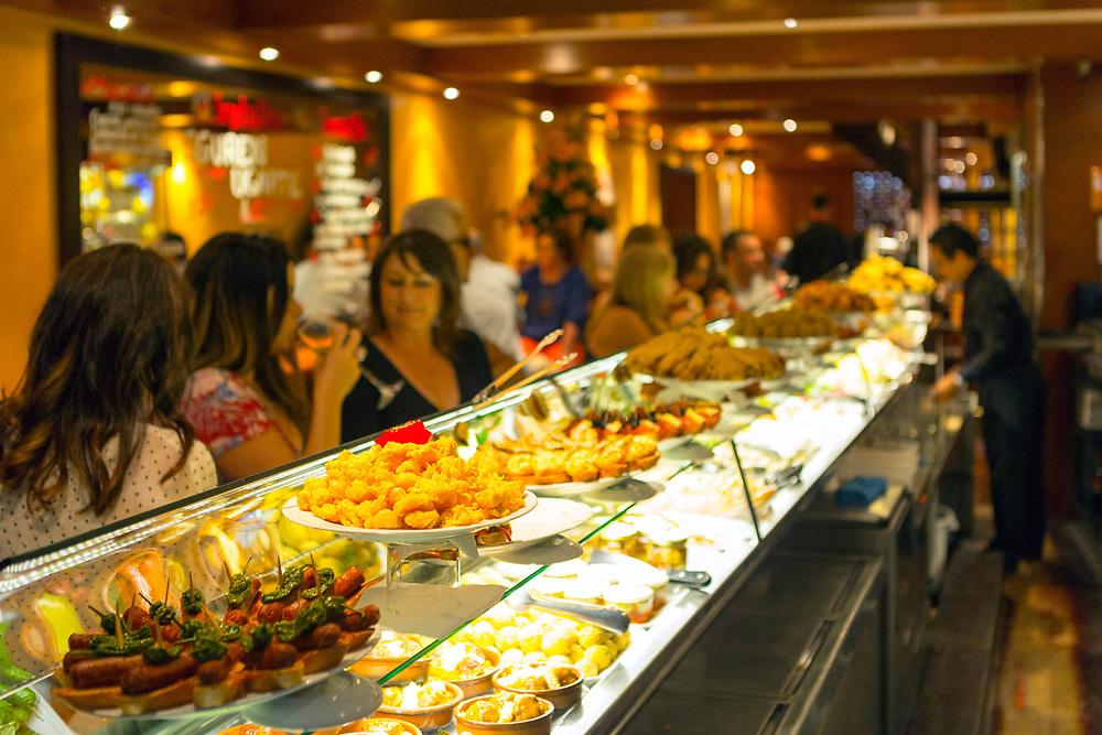 SANTIAGO DE COMPOSTELA, SPAIN - 9th of October - Tourists enjoy sampling local cuisine at a tapas bar in Santiago de Compostela, Galicia, Spain.
