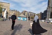Woman wearing a hijab in the centre of Bradford (Yorkshire), England / Femme voilée et anglais d'origine européenne dans le centre de Bradford.