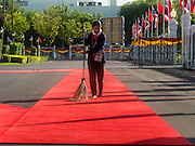 23 JULY 2015 - BANGKOK, THAILAND:    A grounds keeper sweeps the red carpet the Vietnamese and Thai Prime Ministers walked on during the arrival ceremony Thursday. The Vietnamese Prime Minister and his wife came to Bangkok for the 3rd Thailand - Vietnam Joint Cabinet Retreat. The Thai and Vietnamese Prime Minister discussed issues of mutual interest.   PHOTO BY JACK KURTZ
