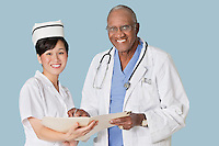 Portrait of happy health care professionals with medical report over light blue background