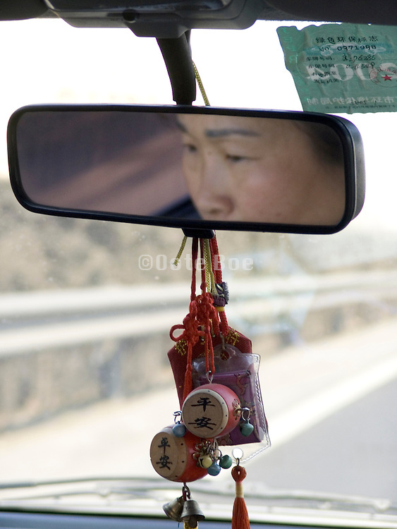 Asian woman seen in the rearview mirror China eyes out off focus