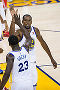 Golden State Warriors forward Kevin Durant (35) high fives Golden State Warriors forward Draymond Green (23) at Oracle Arena in Oakland, Calif., on October 17, 2017. (Stan Olszewski/Special to S.F. Examiner)