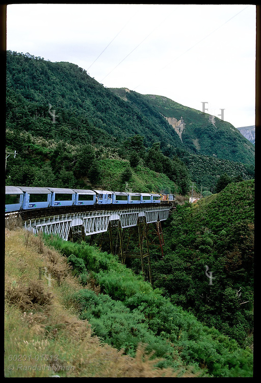 TranzAlpine Express train crosses bridge in Southern Alps as it speeds from Christchurch to Greymouth; New Zealand.