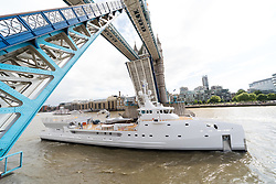 © Licensed to London News Pictures. 14/05/2017. LONDON, UK.  The Game Changer, a newly built superycht support vessel arrives in London on the River Thames under Tower Bridge. The 70-meter superyacht support vessel has a large helideck so that yacht owners can take larger helicopters on long range flights to their mother yachts and 250 square metres of open deck space for tenders and toys, plus offices, facilities and accommodation for 22 crew and staff below deck. Built by Dutch Shipbuilder, Damen, the Game Changer was launched in March this year and recently completed sea trials in the North Sea.  Photo credit: Vickie Flores/LNP