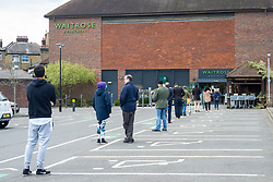 © Licensed to London News Pictures. 28/03/2020. LONDON, UK.  Customers queue in the car park waiting to enter a Waitrose & Partners supermarket in Northwood, north west London.  The supermarket chain has implemented a controlled entry system into its stores which keeps customers 2 metres apart, limits stockpiling and ensures that stock on the shelves remains available for all customers.  Photo credit: Stephen Chung/LNP