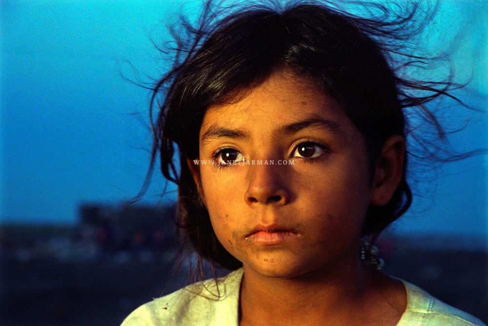 Tamaulipas, Mexico, 1996 – Marisol daydreams at dusk while anticipating the arrival of more garbage trucks at the municipal garbage site where she and siblings search for recyclable items to support their family's income.
