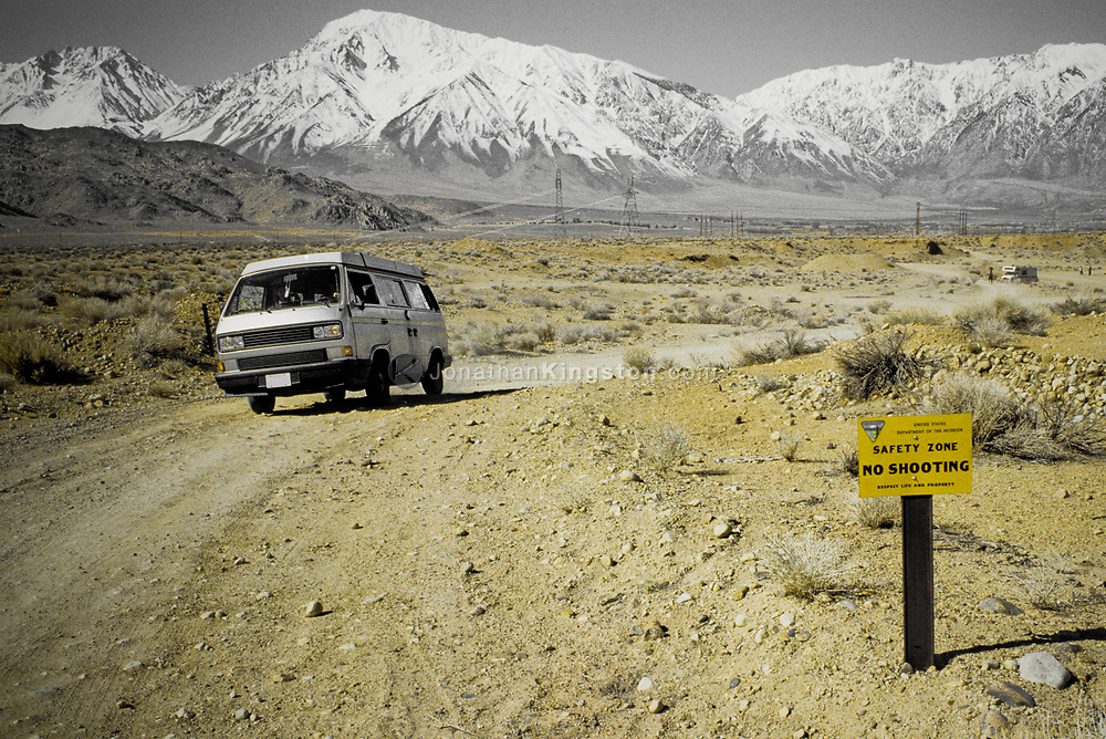 VW van on a dirt road with the Sierra Nevada mountains in the background, Bishop, California.