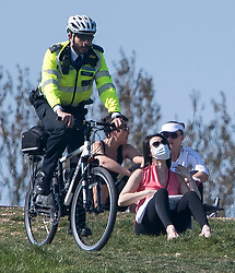 © Licensed to London News Pictures. 15/04/2020. London, UK. Police officers on bike ride past people sitting down on Primrose Hill, North London, during a pandemic outbreak of the Coronavirus COVID-19 disease. The public have been told they can only leave their homes when absolutely essential, in an attempt to fight the spread of coronavirus COVID-19 disease. Photo credit: Ben Cawthra/LNP
