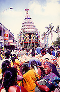 IM# 003:The Great Temple car festival of Sri Kapaleeswarar Temple,Mylapore,Chennai,Tamilnadu,india.The women are clad in silk sarees and one of them is seen using a mobile phone.The bullock cart carries the wooden breaks for the temple car.