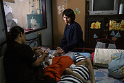 Preeyanan Lorsermvattana sits in the bedroom of a mother and son whom she assisted in receiving compensation after a hospital doctor injected the pregnant mother with a drug that led to the child being born severely mentally and physically disabled. Now 9 years old she continues to help the family. After she suffered personally during the birth of her son which left him having to have a prosthetic hip and received no compensation she made it her mission to help others.