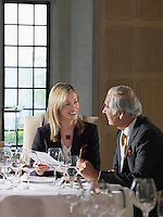 Business man and woman sitting at restaurant table talking