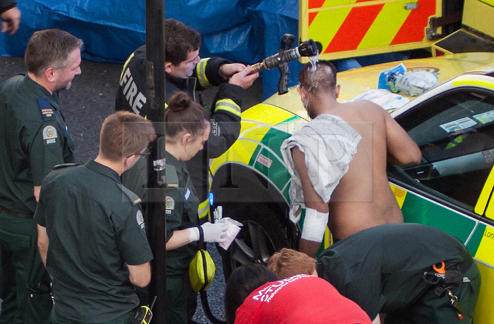 © Licensed to London News Pictures. 25/07/2017. London, UK. A victim of what is thought to have been an acid attack, has water poured on his head by a fireman - on the side of the road in Bethnal Green. Two men have been taken to hospital after flagging down police for help. Photo credit: Liam Creighton/LNP