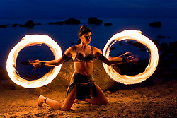 Woman fire dancer twirls torches. Fire on the move.