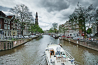Boat rides through the canal near Westerkerk Church in Amsterdam.