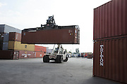 Shipping containers and forklift at a port awaiting export