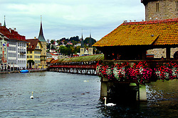 The Chapel Bridge (Kapellbrücke) is a covered wooden footbridge spanning across the Reuss River.