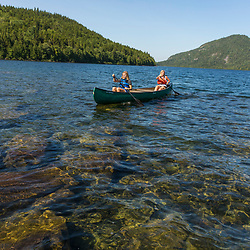 A woman and her daughter paddle a canoe on Deboullie Pond in Aroostook County, Maine. Deboullie Public Reserve Land.