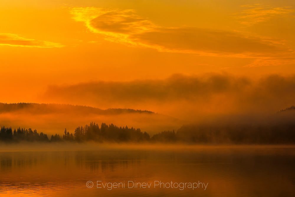 Fiery mist and cluds by the lake at sunrise