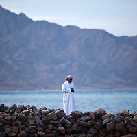 "An Egyptian man prays at sunset in Dahab, Egypt. The Blue Hole is notorious for the number of diving fatalities which have occurred there, earning it the sobriquet ""World's Most Dangerous Dive Site"" and the nickname ""Diver's Cemetery"". The site is signposted by a sign that says ""Blue hole: Easy entry"". Accidents are frequently caused when divers attempt to find the tunnel through the reef (known as ""The Arch"") connecting the Blue Hole and open water at about 52 m depth. According to dive experts roughly 10 people die each year. April 2012."