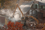 Excavators work from on top of the rubble pile to tear down the remaining portions of the former Holy Childhood school building in Harbor Springs.