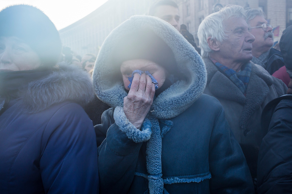 KIEV, UKRAINE - JANUARY 26: A woman weeps as a casket containing the body of Mikhail Zhiznevsky, 25, an anti-government protester who was killed in clashes with police, is carried past on January 26, 2014 in Kiev, Ukraine. After two months of primarily peaceful anti-government protests in the city center, new laws meant to end the protest movement have sparked violent clashes in recent days. (Photo by Brendan Hoffman/Getty Images)