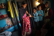 A woman shows other family members a sari from one of three cabinets that are part of the dowry of teenager Suman Kumari on the day of her wedding, at her family's home in the village of Bakarour in the state of Bihar, India.  The dowry also included 100,000 rupees, about $2,000US.