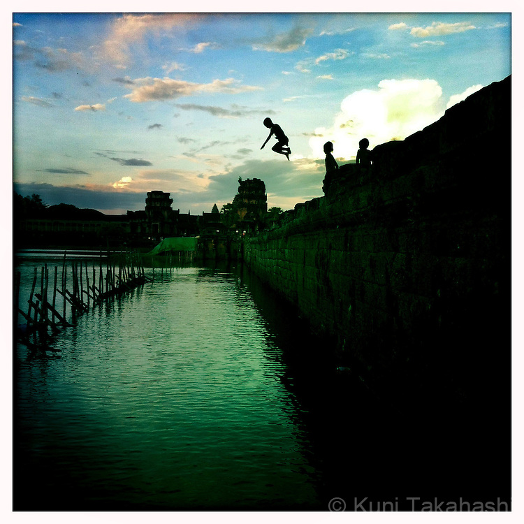 (SIEM REAP, CAMBODIA - MAY 29, 2012)<br /> A boy jumps in the water in Angkor Wat temple complex in Siem Reap, Cambodia on May 29 2012. After 25 year of isolation, Cambodia opened to tourists in the mid-1990s and tourist&rsquo;s numbers have increased every year since - the country seeing more than a million tourists in 2011.<br /> (Photo by Kuni Takahashi)