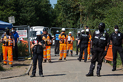 Harefield, UK. 26 June, 2020. HS2 security guards stand in front of a road closure as they observe activists from HS2 Rebellion and Extinction Rebellion UK taking part in a 'Rebel Trail' hike along the route of the HS2 high-speed rail link. The activists, who departed from Birmingham on 20th June and will arrive outside Parliament in London on 27th June, are protesting against the environmental impact of the high-speed rail link and questioning the viability of the £100bn+ project.