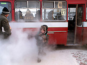 Child with an ice cream in front of Yakutsk bus moving away from the fumes of the car. Yakutsk is a city in the Russian Far East, located about 4 degrees (450 km) below the Arctic Circle. It is the capital of the Sakha (Yakutia) Republic (formerly the Yakut Autonomous Soviet Socialist Republic), Russia and a major port on the Lena River. Yakutsk is one of the coldest cities on earth, with winter temperatures averaging -40.9 degrees Celsius.