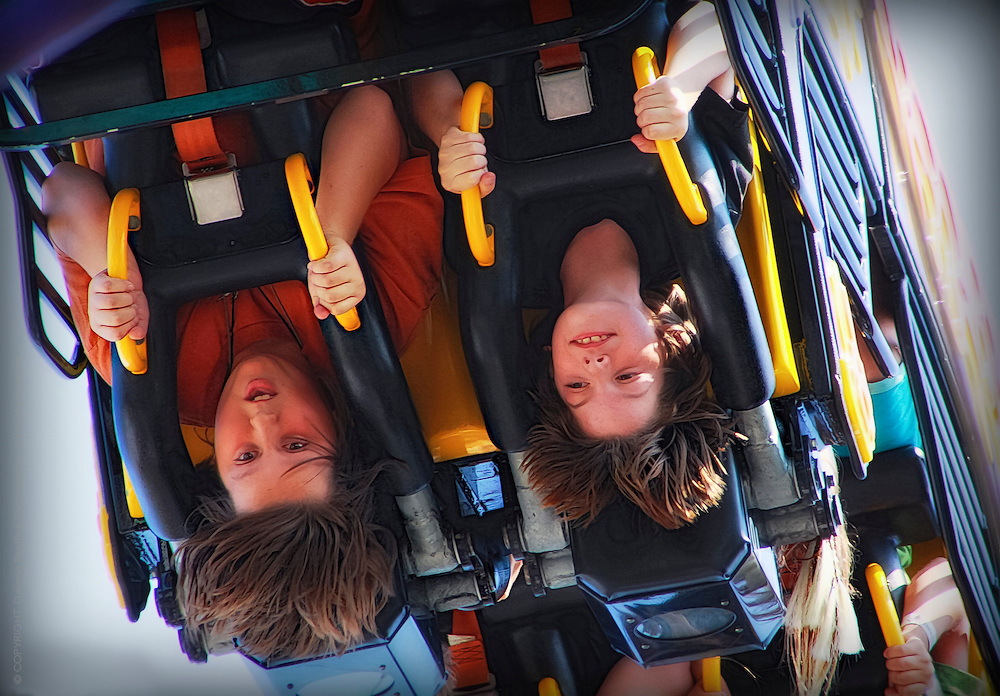 candid action: children on roller coaster ride hanging upside down